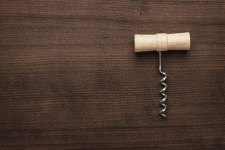 uncork: retro wooden corkscrew on the brown table