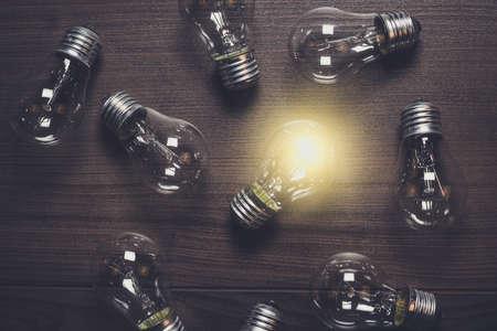 leuchtenden Glühbirne über hölzerne Hintergrund Einzigartigkeit Konzept