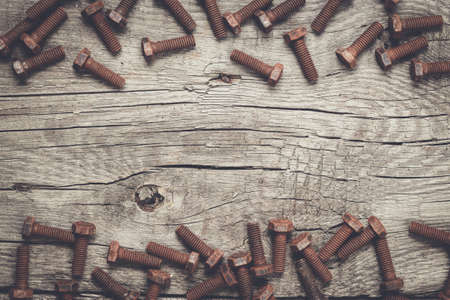 gudgeon: old rusty screw bolts on the wooden table background