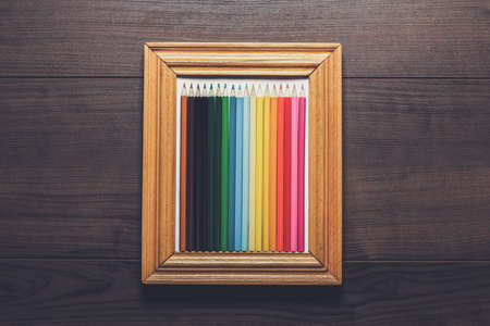 yeloow: multicolored pencils in a frame over wooden background