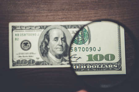 authentication: one hundred dollars banknote authentication on wooden background