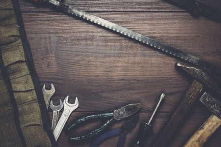 screw key: rusty construction instruments on the wooden background