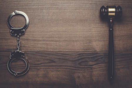 trickster: handcuffs and judge gavel on brown wooden background Stock Photo
