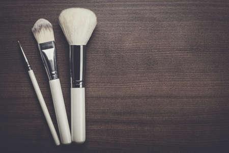 brosses de maquillage blanc sur fond en bois brun