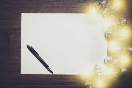 hoja en blanco: Bombillas brillantes y hoja de papel en blanco sobre fondo de madera