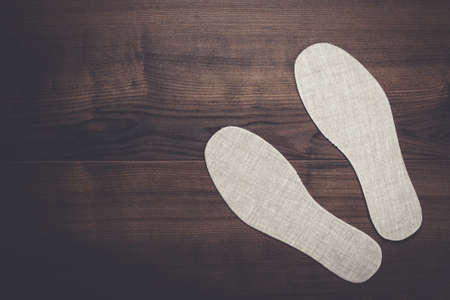 insoles: grey insoles for shoes over wooden background