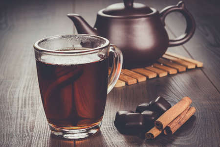 trivet: cup of tea with cinnamon sticks and teapot on the table Stock Photo