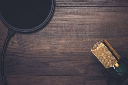 Vintage mikrofon kondensacji i filtr pop na drewnianym tle