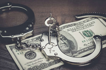 handcuffs: handcuffs and one hundred dollars on the wooden table