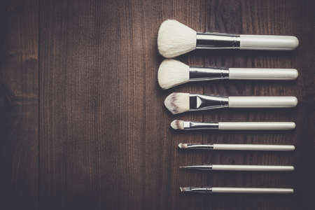maleza: white make-up brushes on brown wooden table