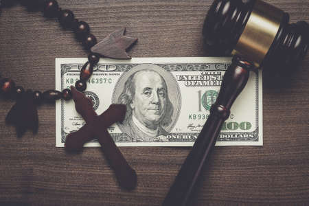 belief system: wooden cross gavel and money on brown table background concept Stock Photo