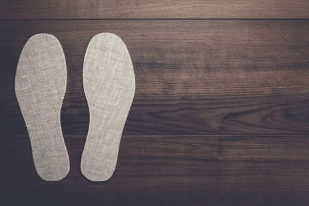 inner wear: grey insoles for shoes on wooden background