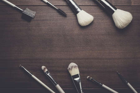 cosmetics background: make-up brushes on the brown wooden background Stock Photo