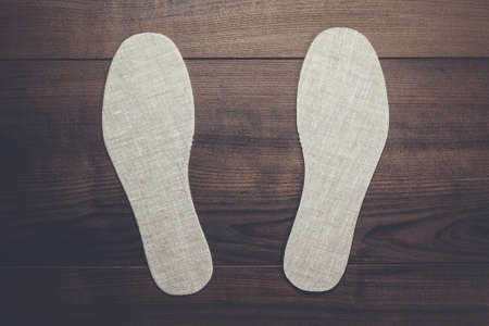 wooden insert: grey insoles for shoes over wooden background