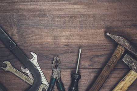 screw key: rusty construction tools on the wooden background