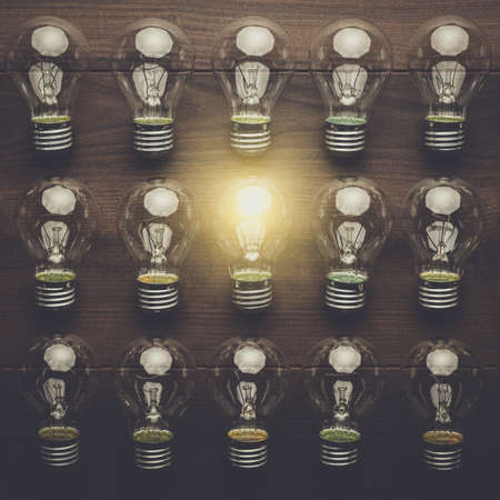 multiple objects: glowing bulb uniqueness concept on brown woodentable