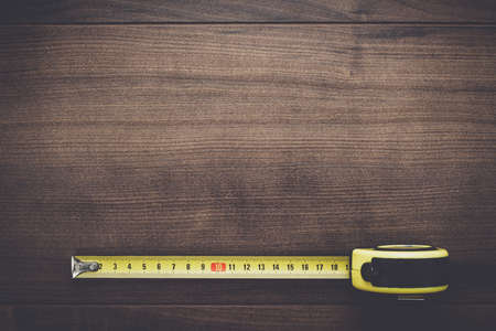 cinta métrica en el fondo de madera marrón