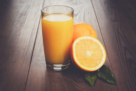 vaso de jugo: fresh orange and glass with juice on the brown wooden table