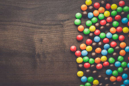 topple: colorful sweets on the brown wooden table background