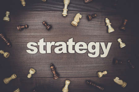 creative concept: word strategy and chessmen on the brown wooden background Stock Photo