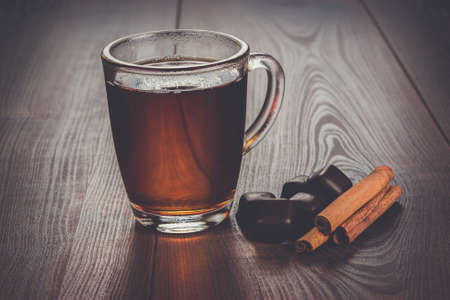 trivet: cup of tea with cinnamon sticks and chocolate on the table Stock Photo