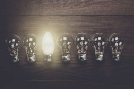 uniqueness: glowing bulb uniqueness concept on brown woodentable