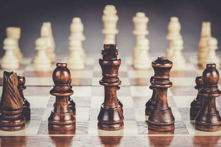 wooden board: chess board with figures on the brown table background