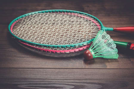 racket: shuttlecock and badminton racket on brown wooden background Stock Photo