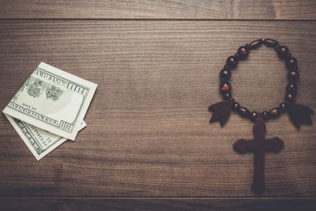 belief system: wooden cross and money on brown table background