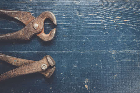 pinchers: old rusty tongs on blue wooden background