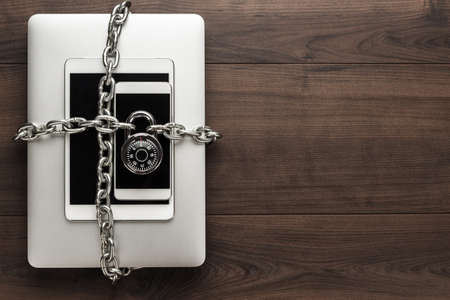 pad lock: data security concept: computer, tablet, phone bound by metal chain and closed with combination lock on wooden table