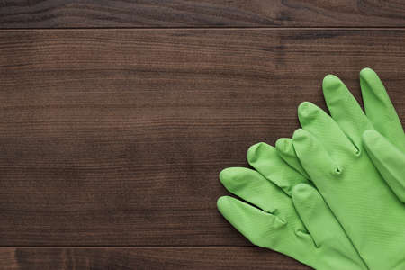 toxic: green rubber cleaning gloves on wooden background