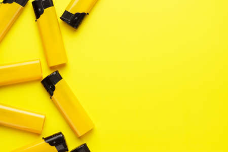 encendedores: disposable plastic lighters on the yellow background Foto de archivo