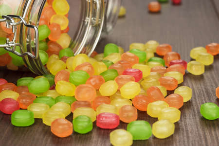 overturn: toppled over glass jar full of colorful sweets on the wooden table