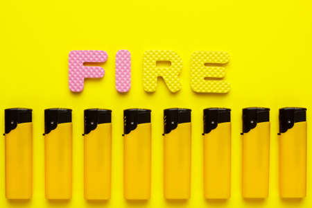 encendedores: encendedores desechables de plástico y el fuego de la palabra sobre fondo amarillo