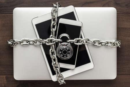 beveiliging van gegevens concept: computer, tablet, telefoon gebonden door metalen ketting en afgesloten met cijferslot op houten tafel