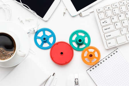 workflow and teamwork concepts with colorful gears different gadgets and office stationery on the white office table Stock Photo