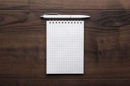 writes: blank notebook and white pen on the brown wooden table