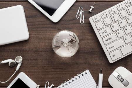 online freelance-concept werken. wereldbol met verschillende gadgets en briefpapier op de houten kantoortafel. wereldwijde markt