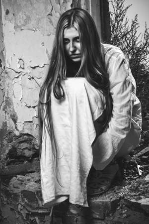 photo of zombie girl sitting in abandoned building