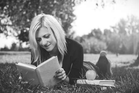 photo of student girl reading on grass