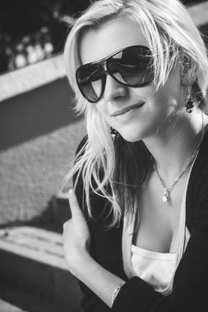 photo of girl in sunglasses sitting on stairs
