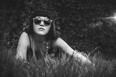 beautiful girl wearing sun glasses over foliage background