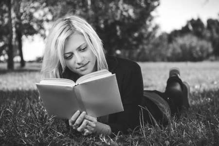 beautiful girl reading in park on grass photo