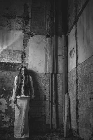 zombie girl with loong hair in an abandoned building holding knife 免版税图像
