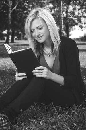blond student girl reading book on grass photo