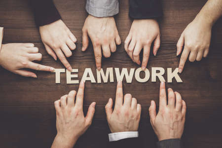 metaphor: Teamwork concept. Different hands of men and women connect letters into one word on the brown wooden table background.