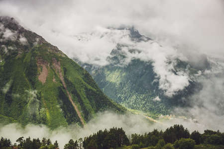 dombay: mountains with green grass and stormy sky landscape Stock Photo