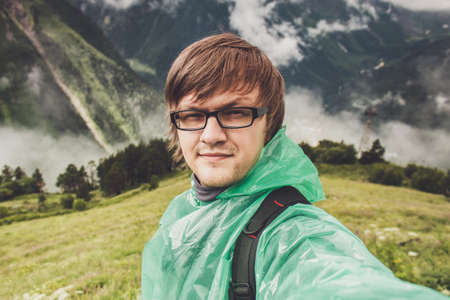 dombay: man in glasses taking selfie. mountains with green grass in background Stock Photo