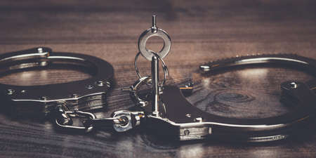 wristlets: handcuffs and keys on the brown wooden table background